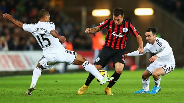 Eduardo Vargas of QPR goes between Wayne Routledge and Leon Britton of Swansea City (R) during the Premier League match between Swansea City and QPR at Liberty Stadium on December 2, 2014 in Swansea, Wales. (Getty Images)