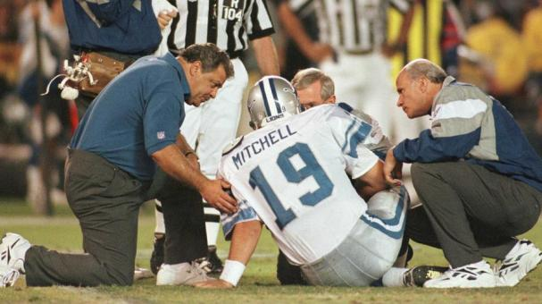 Scott Mitchell of the Detroit Lions is helped by head coach Wayne Fontes (left) and medical staff after being hit hard by the San Diego Chargers defense during the Monday Night game at Jack Murphy Stadium in San Diego, California. 11 Nov 1996 Getty Images