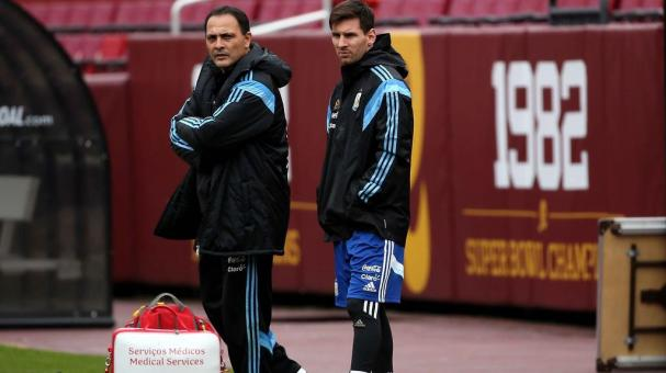 Lionel Messi (right) of the Argentinian national soccer team sits on the bench as his teammates practice on the field in preparation to take on El Salvador at FedExField on March 27, 2015 in Landover, Maryland. (Getty Images)