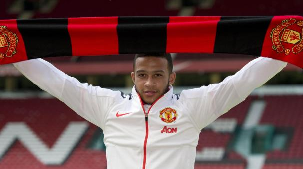 Memphis Depay poses with a scarf for a photograph as he is officially unveiled as a Manchester United player at Old Trafford stadium in Manchester, on July 10, 2015. Getty Images
