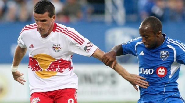 Sebastien Le Toux #9 of the New York Red Bulls battles with Collen Warner #18 of the Montreal Impact to keep possession of the ball during the match at the Saputo Stadium in Montreal, Quebec, Canada. (Getty Images)