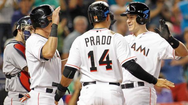 J.T. Realmuto (R) of the Miami Marlins celebrates with teammates including Martin Prado #14 at home plate after his sixth inning grand slam home run against the Boston Red Sox at Marlins Park on August 12, 2015 in Miami, Florida. (Getty Images)