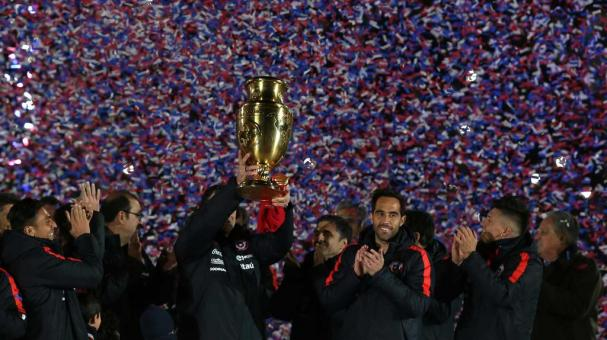 Chile's team players pose with the Copa America Centenario trophy during a celebration at the National Stadium in Santiago, on July 3, 2016. / AFP / CLAUDIO REYES (Photo credit should read CLAUDIO REYES/AFP/Getty Images)
