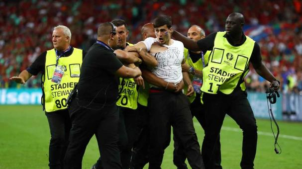 PARIS, FRANCE - JULY 10: A pitch invader is led off by stewards during the UEFA EURO 2016 Final match between Portugal and France at Stade de France on July 10, 2016 in Paris, France. (Photo by Lars Baron/Getty Images)