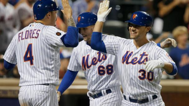 Michael Conforto #30 of the New York Mets celebrates his eighth inning three run home run against the San Francisco Giants with teammates Jeff McNeil #68 and Wilmer Flores #4 at Citi Field on August 21, 2018. Getty Images