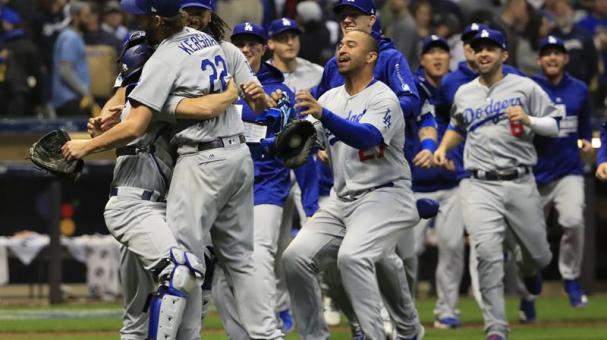 Los Angeles Dodgers pitcher Clayton Kershaw (2-R) gets a hug by Los Angeles Dodgers catcher Austin Barnes (L) and teammates celebrate after defeating the Milwaukee Brewers in the National League Championship Series game seven. EFE