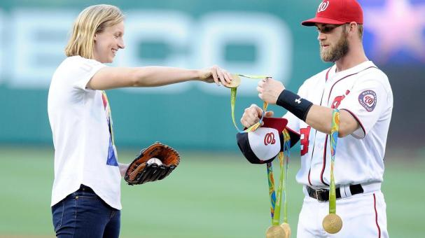 Katie Ledecky hands her Olympic medals to Bryce Harper #34 before throwing out the opening pitch before the game between the Baltimore Orioles and the Washington Nationals at Nationals Park on August 24, 2016 in Washington, DC. (Getty Images)