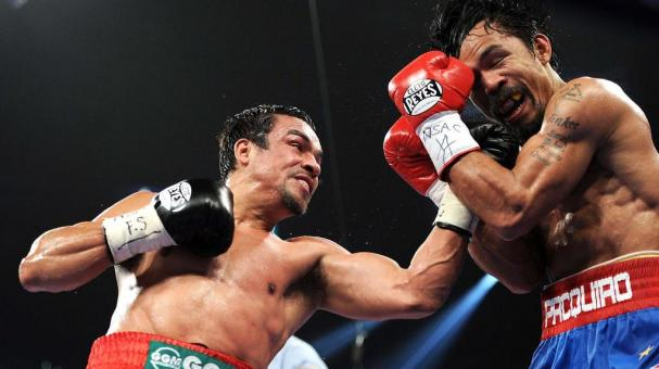 Juan Manuel Marquez throws a left to the face of Manny Pacquiao during the WBO world welterweight title fight at the MGM Grand Garden Arena on November 12, 2011 in Las Vegas, Nevada. (Getty Images)