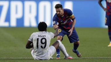 Lionel Messi of FC Barcelona helps Alphonso Davies of FC Bayern Munich during the UEFA Champions League Quarter Final match between Barcelona and Bayern Munich at Estadio do Sport Lisboa e Benfica on August 14, 2020 in Lisbon, Portugal. (Getty Images)