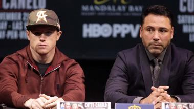 Saul 'Canelo' Alvarez and promoter Oscar De La Hoya listen to former WBC Middleweight World Champion Miguel Cotto, Puerto Rico during their press conference in Las Vegas, Nevada on November 18, 2015. (Getty Images)