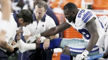 Dez Bryant is tended to on the sideline after injuring his foot during the second half. (AP)