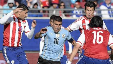 Uruguay's defender  Maximiliano Pereira vies for the ball with Paraguay's midfielders Nestor Ortigoza, Paraguay's midfielder Osmar Molinas and Paraguay's forward Nelson Haedo Valdez in La Serena, Chile, on June 20, 2015. (Getty Images)