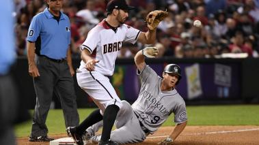 DJ LeMahieu #9 of the Colorado Rockies slides safely into third base after hitting a triple as Adam Rosales #9 of the Arizona Diamondbacks  at Chase Field on September 11, 2017 in Phoenix, Arizona. (Getty Images)