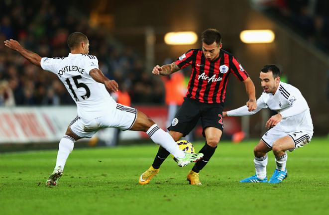 Eduardo Vargas of QPR goes between Wayne Routledge and Leon Britton of Swansea City (R) during the Barclays Premier League match between Swansea City and Queens Park Rangers at Liberty Stadium on December 2, 2014 in Swansea, Wales. (Getty Images)